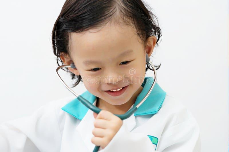 Pojkekläderdoktorn och bruksstethescope med leende och omsorg vänder mot på arkivbild