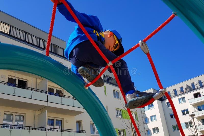 pojkeklättringar på repen i lekplatsen arkivfoton