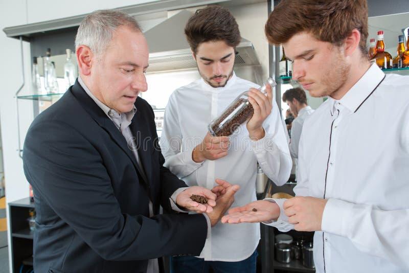 Pojkelärlingar som smeling bönor för aromarabicakaffe arkivbilder