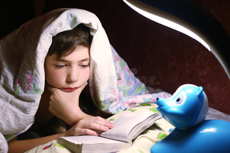 Pojkeläsebok under filten i natttimme royaltyfria bilder