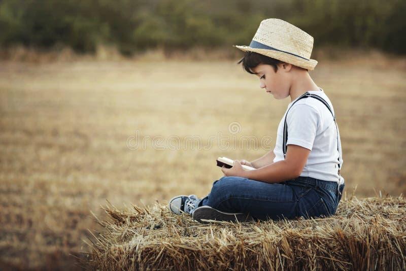 Pojkeläsning en boka arkivfoto