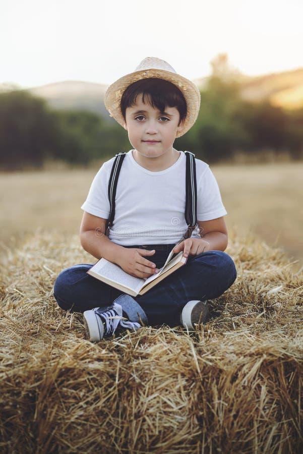 Pojkeläsning en boka royaltyfri bild