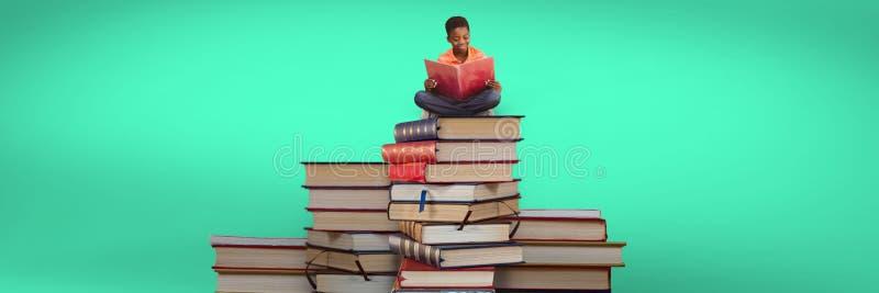 Pojkeläsning och sammanträde på en hög av böcker och grön bakgrund arkivbild
