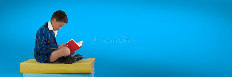 Pojkeläsning och sammanträde på en hög av böcker med blå bakgrund royaltyfria foton