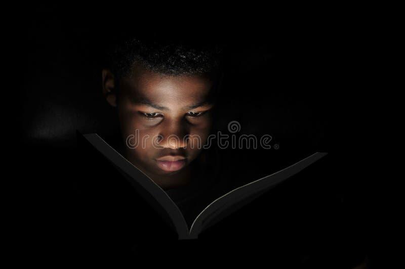 Pojkeläsning på natten arkivbilder