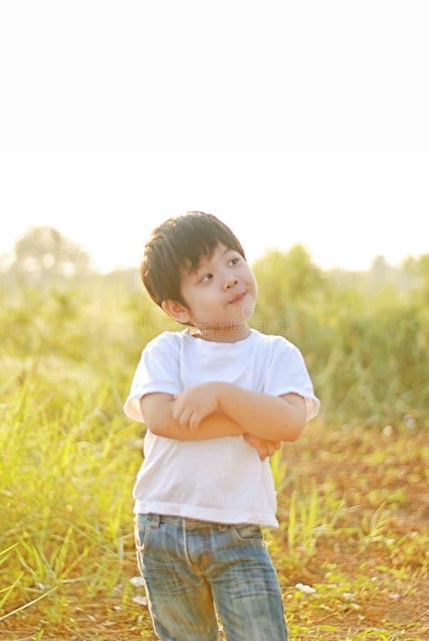 Pojkeleende som är lyckligt i morgonen, finns det en trädgård royaltyfri bild
