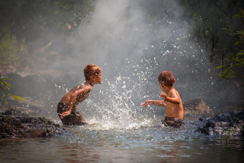 Pojkelek i vatten - färgstänkvatten royaltyfri bild