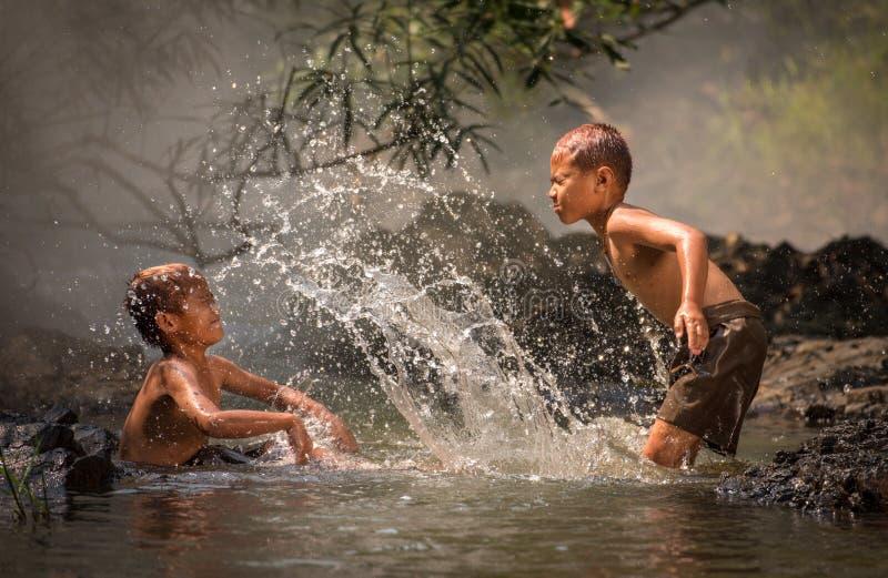 Pojkelek i vatten - färgstänkvatten arkivbilder