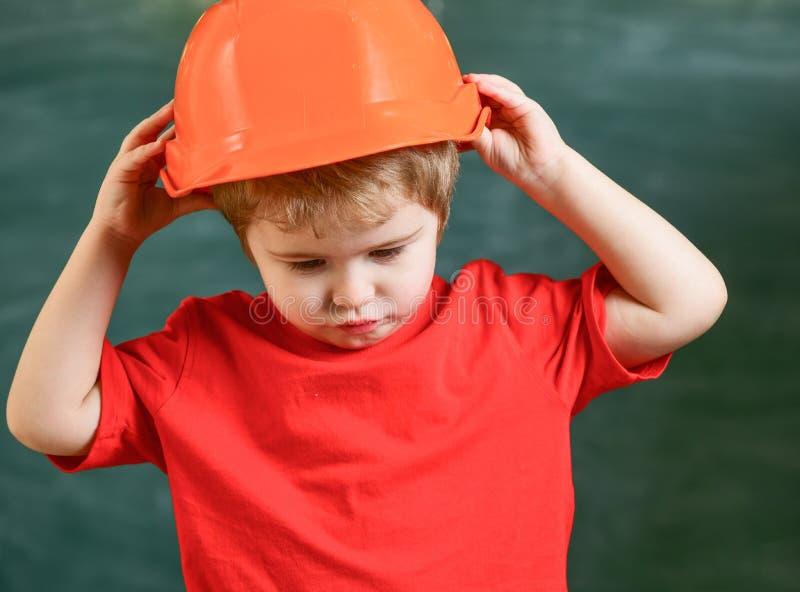 Pojkelek som byggmästare eller arkitekt Lura pojken i orange hård hatt eller hjälmen, svart tavla på bakgrund Barndombegrepp arkivfoton