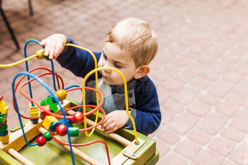 Pojkelekar med en mångfärgad leksak royaltyfria foton