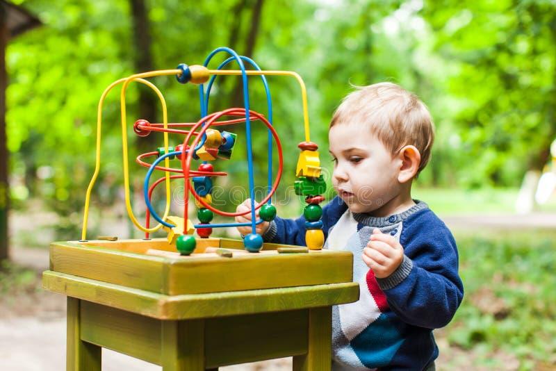 Pojkelekar med en mångfärgad logisk leksak arkivfoton