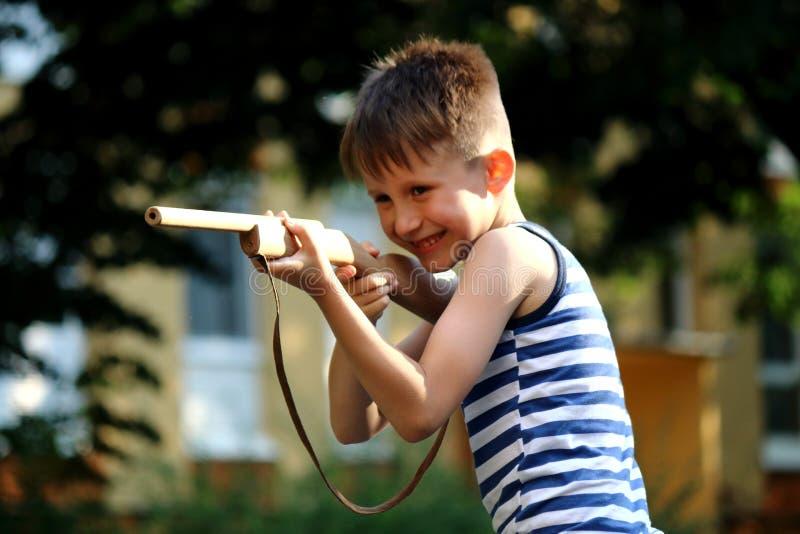 Pojkelekarna med ett trävapen arkivfoto