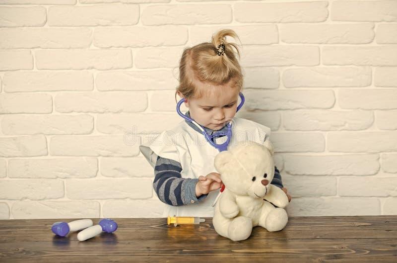 Pojkelekdoktor med nallebjörnen på den vita väggen royaltyfri foto