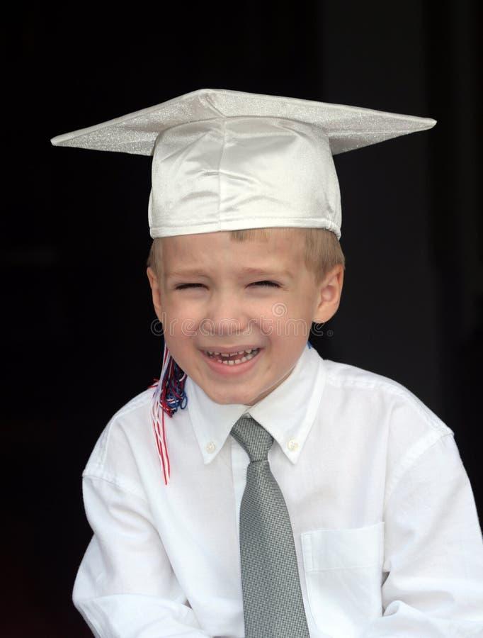 pojkelockavläggande av examen arkivbild