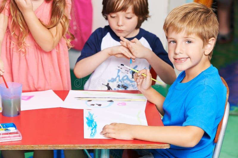 Pojkemålningbild med vattenfärg i skola royaltyfri fotografi