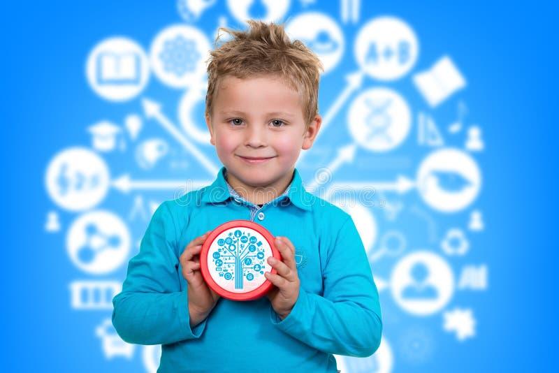 Pojken är den hållande stora klockan, med livlig bakgrund royaltyfria foton