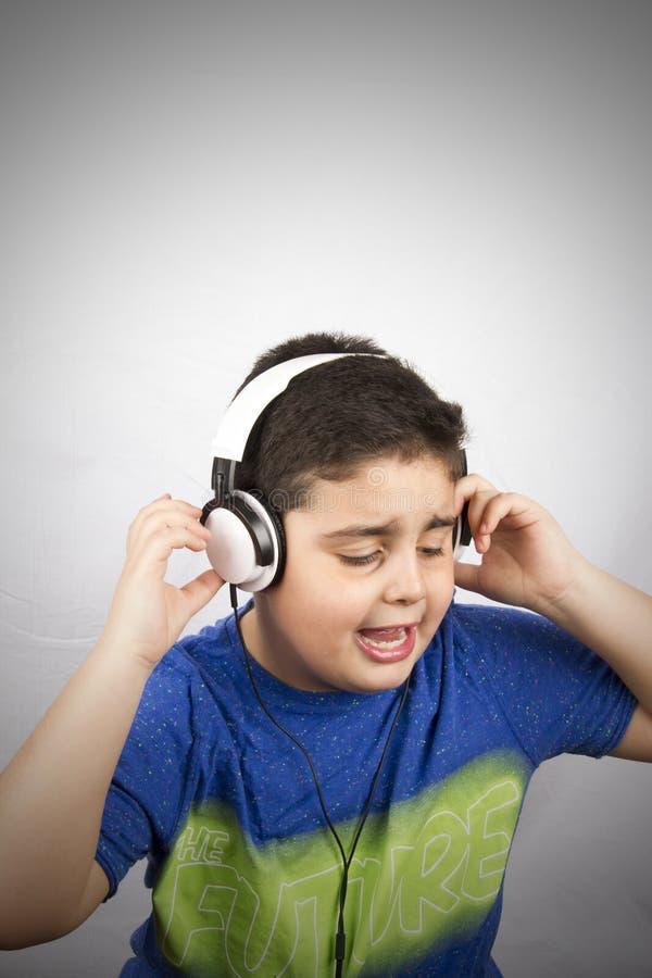 Pojken är lyssnande musik med headphonen fotografering för bildbyråer
