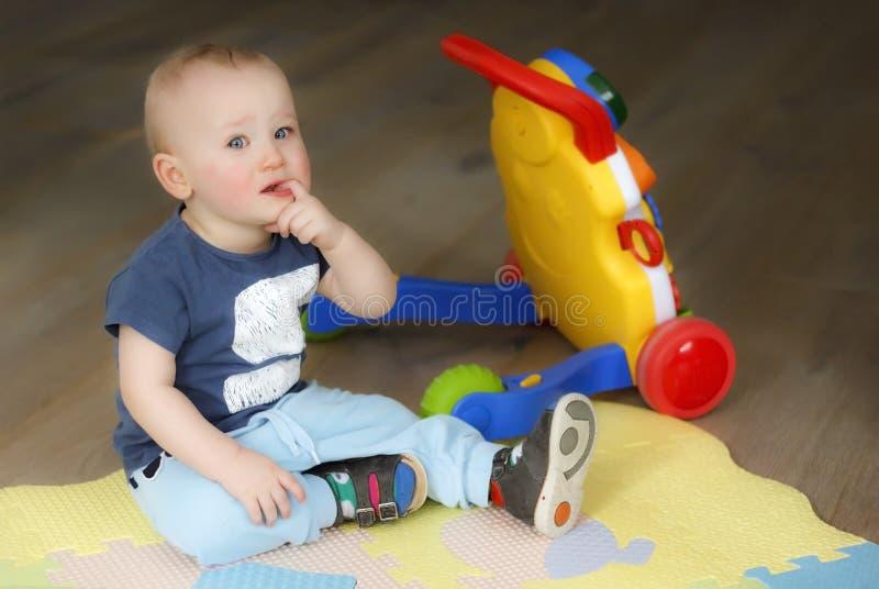 Pojken är upprivet sammanträde på golvet och gråt royaltyfri bild