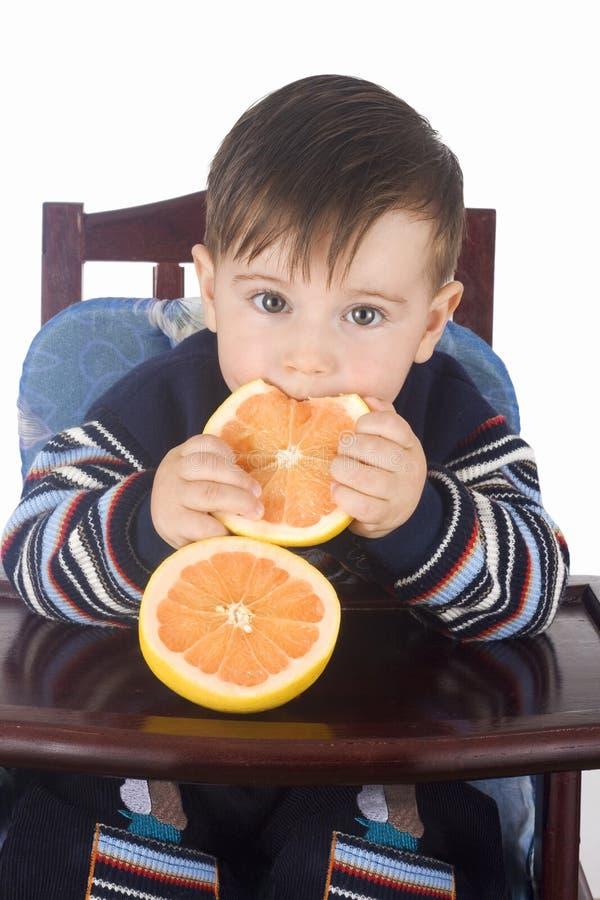 pojken äter den små nya grapefrukten royaltyfri bild