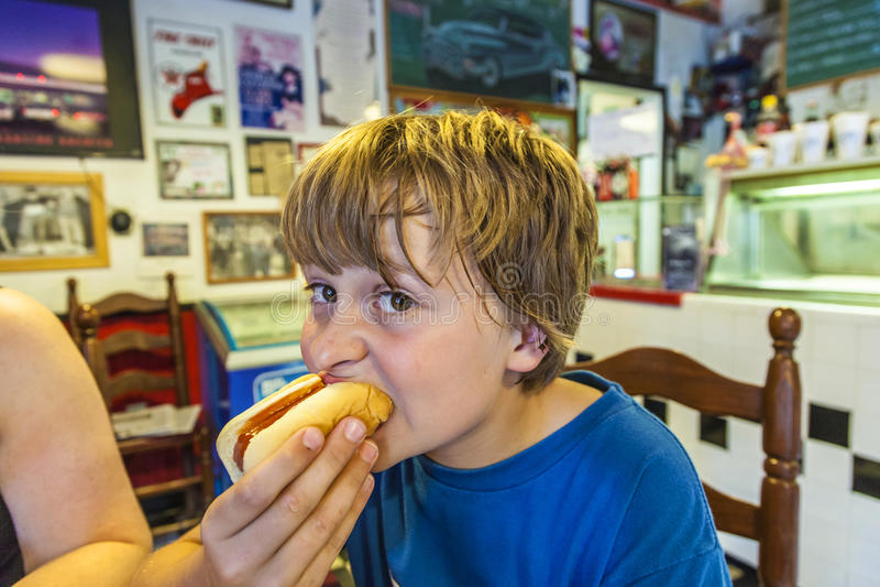 Pojken äter en hotdog i en amerikansk matställe royaltyfri foto