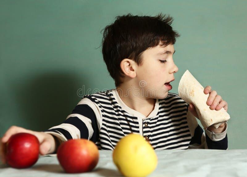 Pojken äter nya äpplen för snabbmatrullavskräden arkivfoto