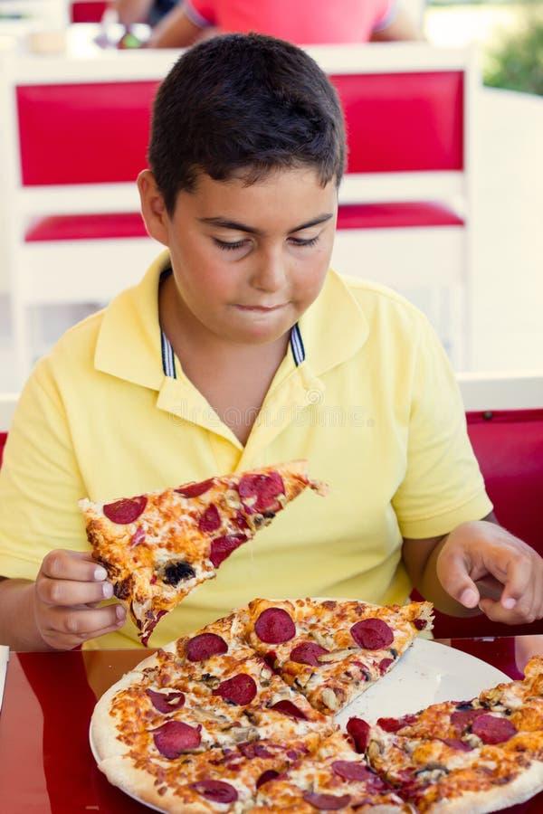Pojken äter pizza arkivfoton