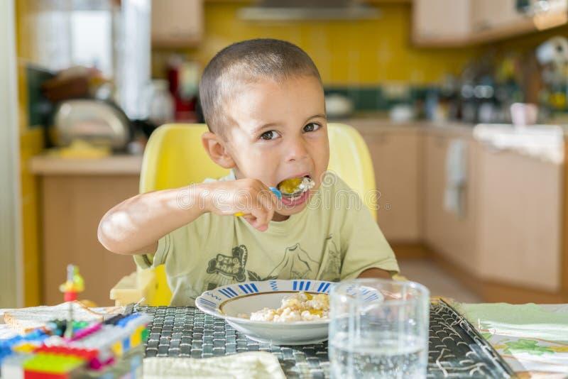 Pojken 2 år äter havregröt Tabell för barn` s Begreppet av självständigheten för barn` s lyckligt äta för pys royaltyfri foto