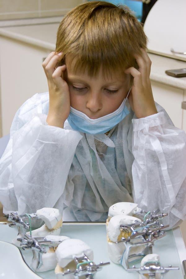 Pojken önskar att vara en orthodontist royaltyfria bilder
