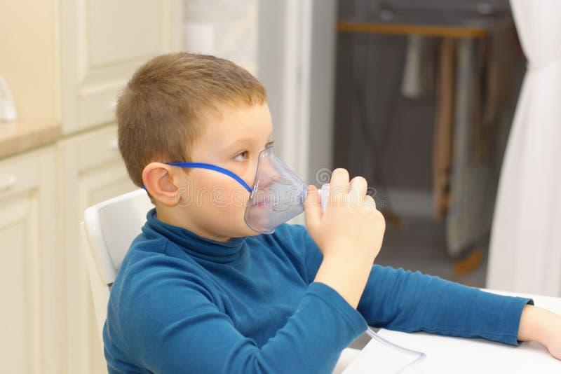 Pojken andas med inhalatorn royaltyfri fotografi