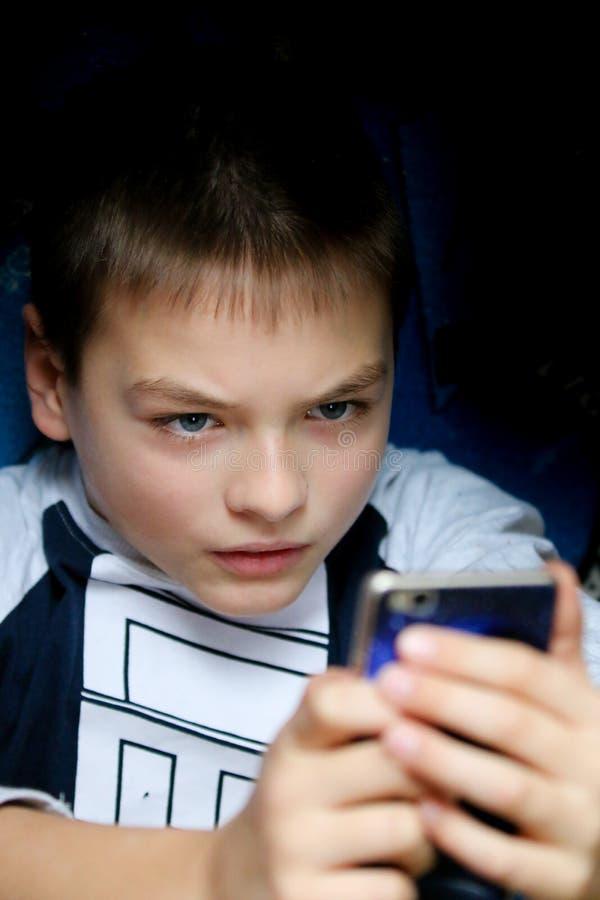 Pojken angås om hans mobiltelefon fotografering för bildbyråer