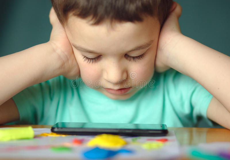Pojken använder smartphonen royaltyfri foto