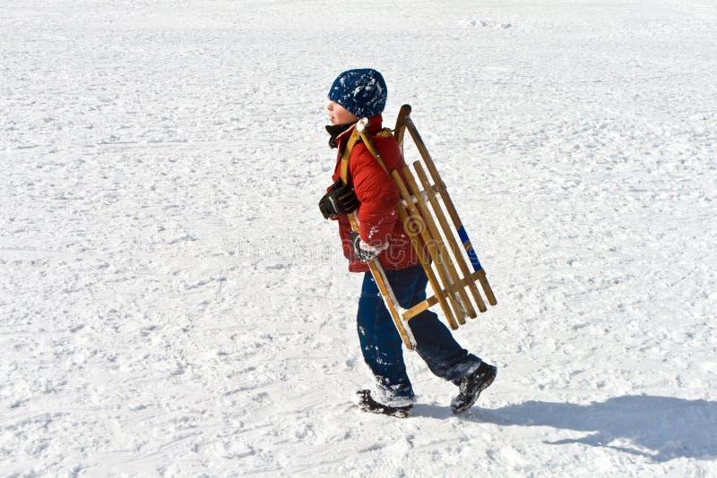 Pojken bär hans kälke i vintrigt landskap royaltyfria bilder