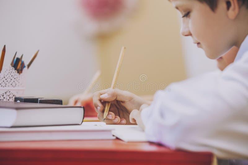Pojken barn i skolan har ett lyckligt, nyfiket, smart arkivfoton