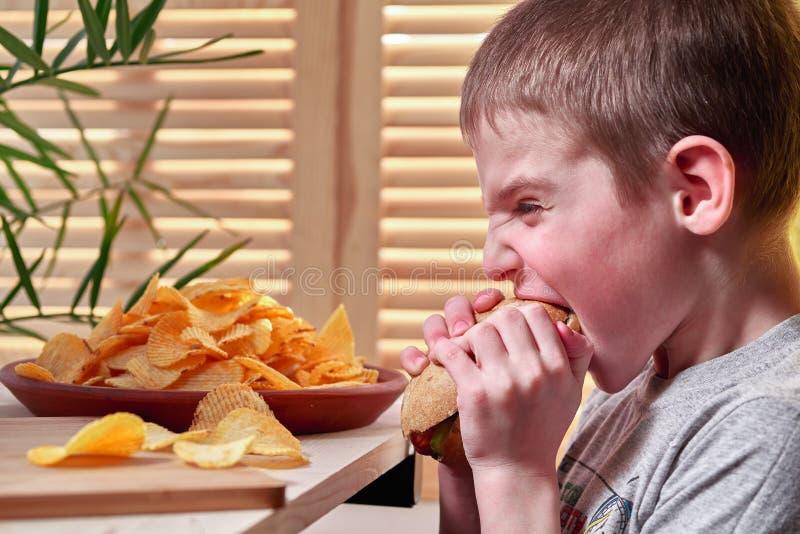 Pojken biter ivrigt den läckra stora varmkorven Barnet äter i en snabbmat royaltyfri bild