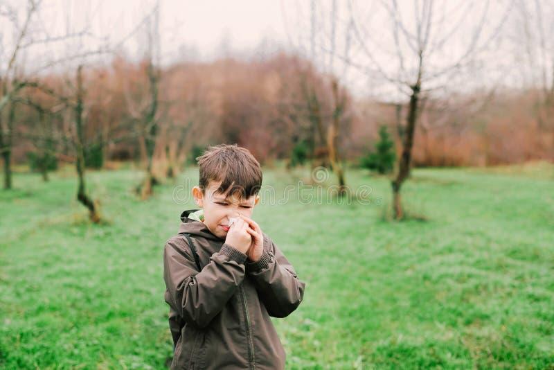 Pojken blåser hans näsa i halsduken Allergin tack vare blommar arkivfoto