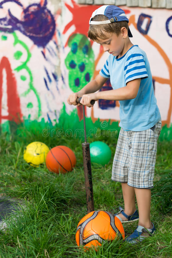 Pojken blåser upp pumpen för fotbollbollen arkivfoto