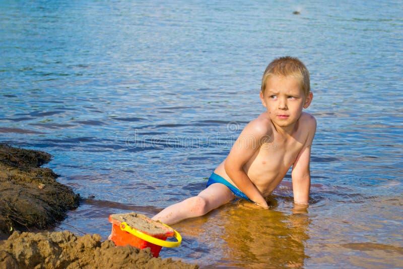 Pojken bygger en sand royaltyfri bild