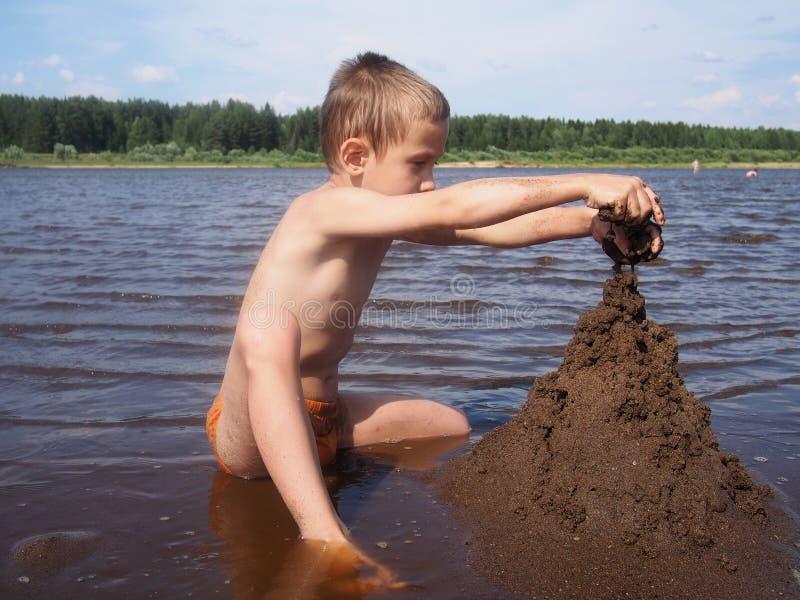 Pojken bygger sandslotten fotografering för bildbyråer