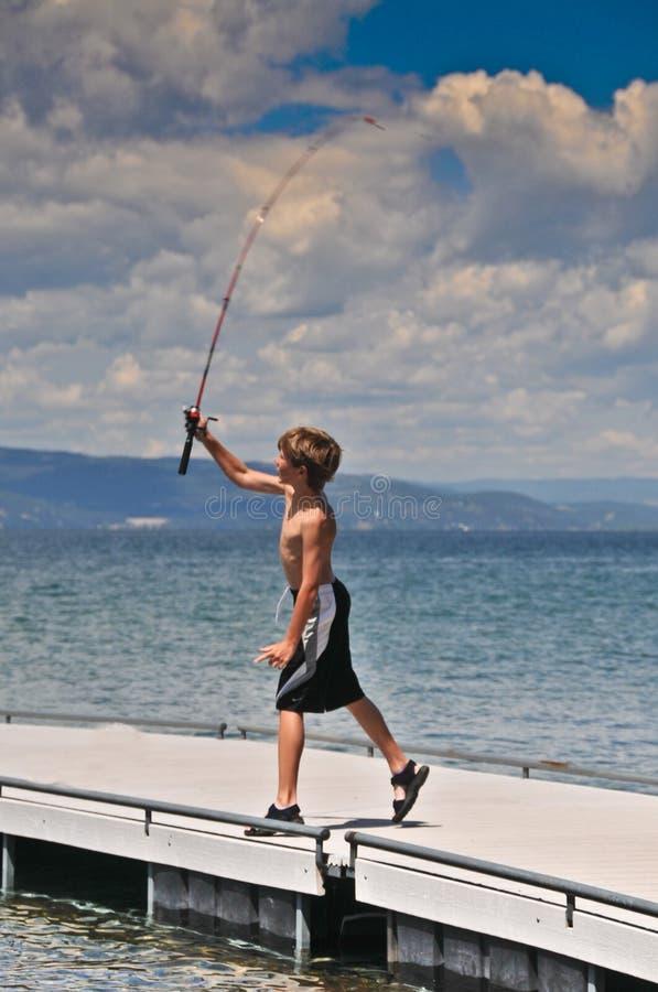 pojken casts fiskerullstången royaltyfri bild