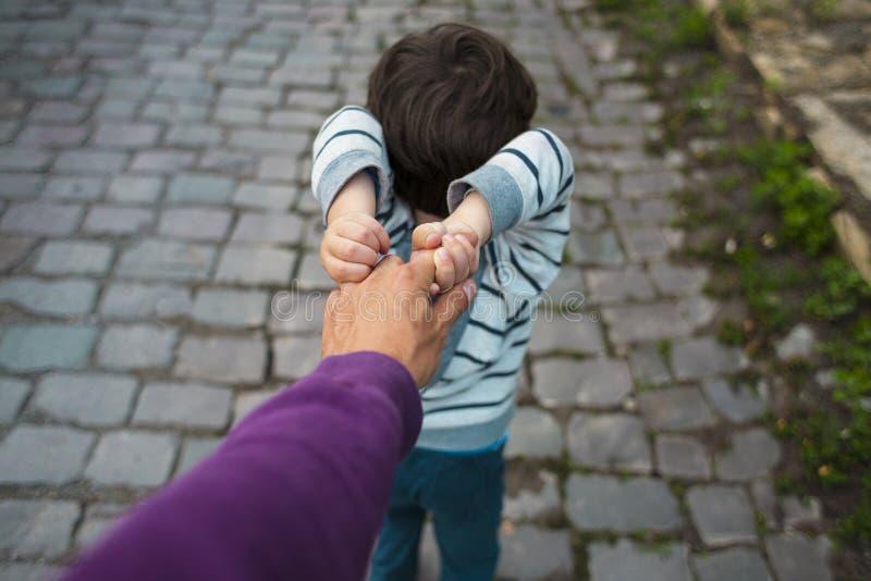 Pojken drar hans hand för fader` s royaltyfri foto