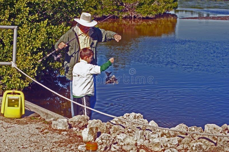 Pojken fångar fisken royaltyfri fotografi