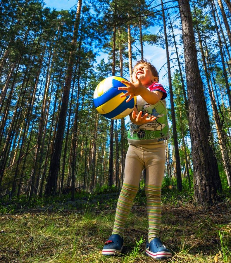 Pojken fångar handbollen in i träna på gräsmatta royaltyfri bild