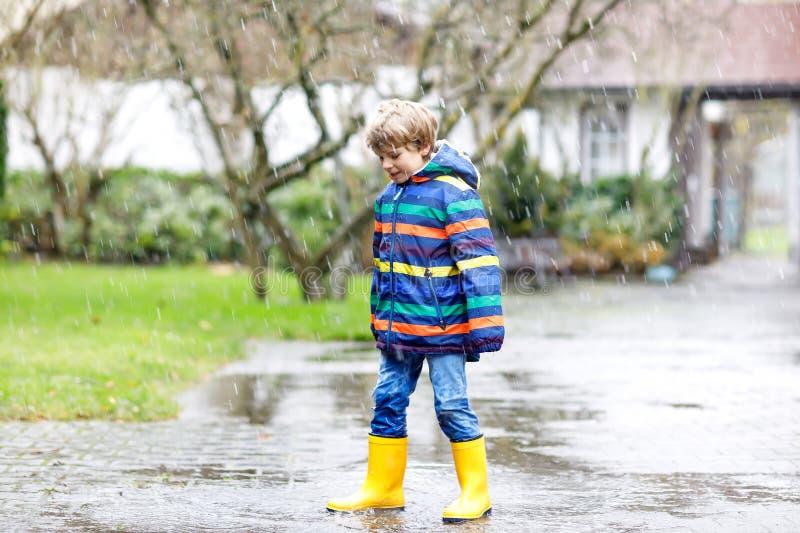 Pojken för den lilla ungen som bär gula regnkängor och går under, regnar snöslask, regnar och snöar på kall dag Barn i färgrikt m royaltyfria foton