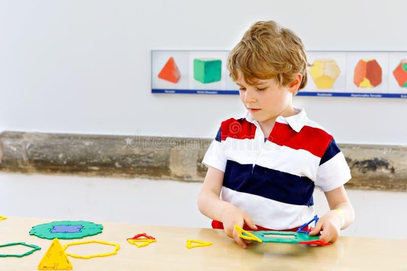 Pojken för den lilla ungen som spelar med massor av färgrik plast-, blockerar satsen i skola eller förträningsbarnkammare roligt  royaltyfria foton