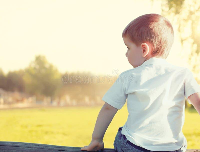 Pojken för det lilla barnet sitter eftertänksamt se bort utomhus royaltyfria bilder