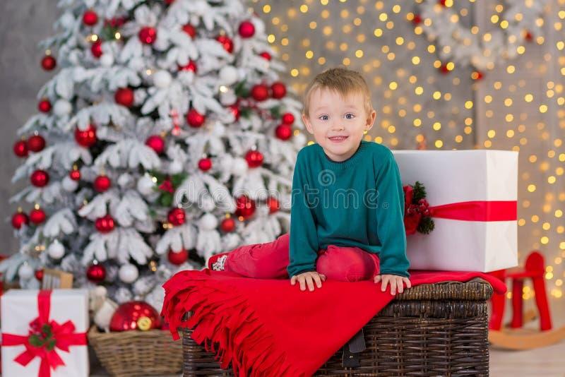 Pojken för julfamiljbarnet som poserar på träasken framlägger nästan, och det vita utsmyckade trädet för det nya året som bär röd arkivbild