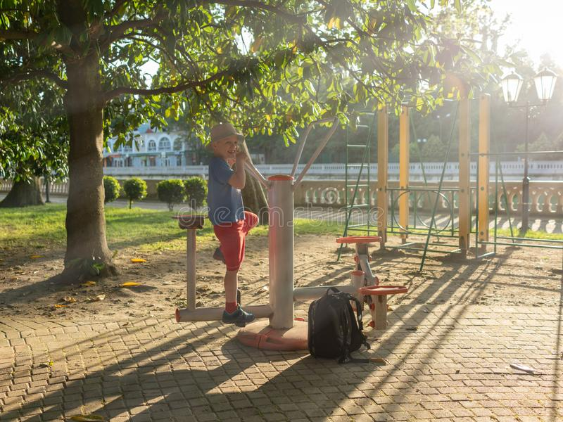 Pojken går in för sportar på gatasportar som malas i strålarna av solnedgången arkivbilder
