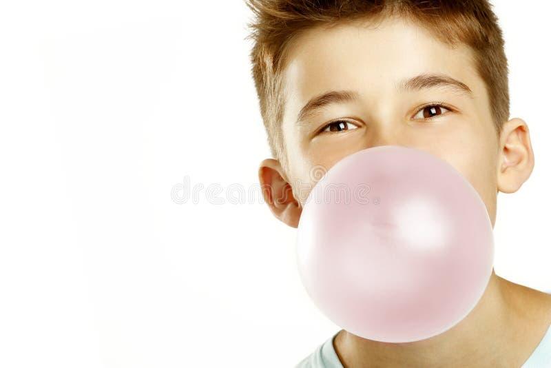 Pojken gör bubblan med tuggning royaltyfria foton