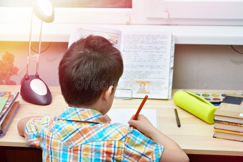 Pojken gör hans läxa på tabellen royaltyfri fotografi