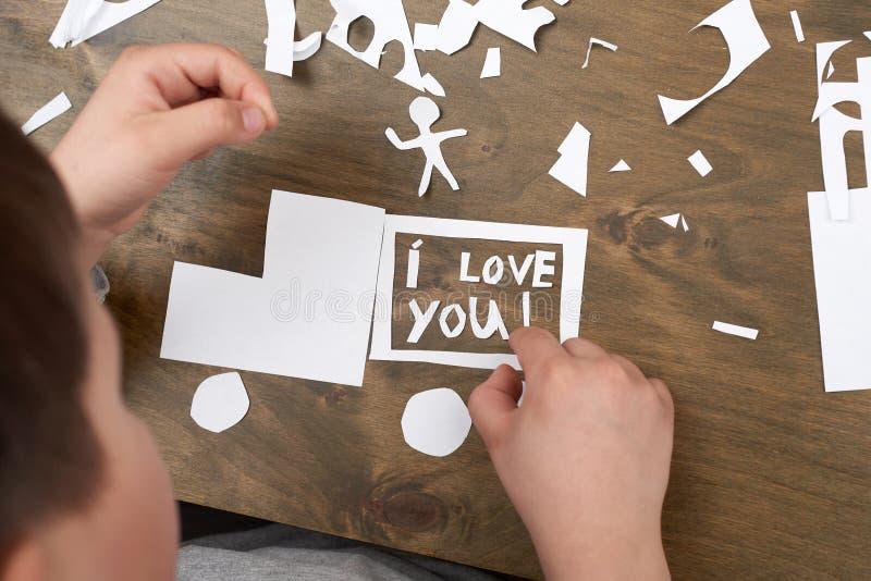 Pojken gör origami - bilen och familjen, barn, förälder, älskar jag dig text, bästa sikt på wood bakgrund royaltyfri foto